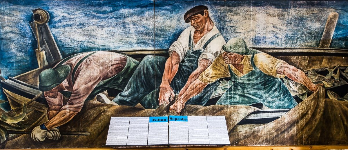 Zoltan Sepeshy (1898-1953) second director of the Cranbrook Art Academy originally painted the mural in the 1930's for the Lincoln Park Post Office near Detroit.  The thirteen-foot long, egg tempura mural, Hauling in the Nets, depicts three brawny fishermen as they struggle to lift a net-load of whitefish into their small open